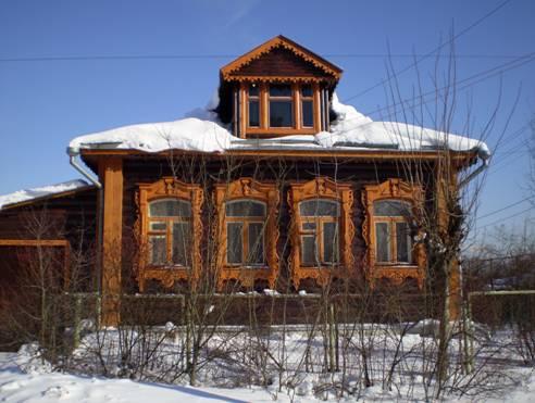 В центре поселка деревенский дом с дивными резными наличниками.